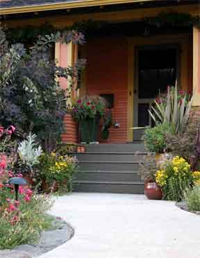 front yard entrance stone containers and flowers